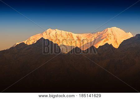 Beautiful first light from sunrise on Mount Kanchenjugha Himalayan mountain range Sikkim India. Orange tint on the mountains at dawn