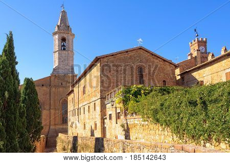 Sunny promenade along the city walls towards the Cathedral in Pienza, Tuscany, Italy