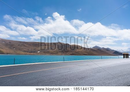sunlight road and holy lake background on tibet plateau