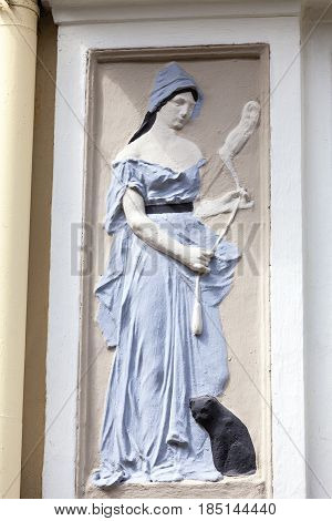 Relief on facade of old building woman in blue dress Prague Czech Republic Europe