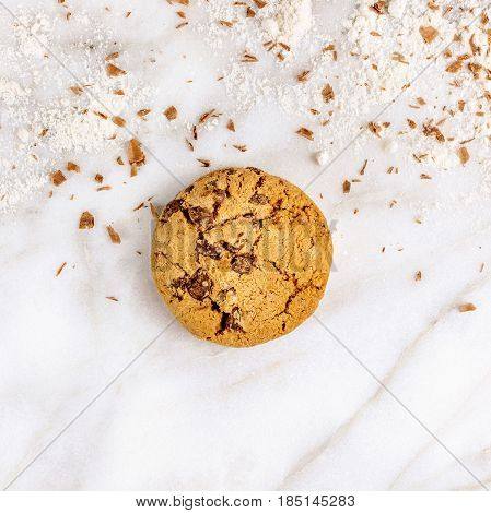 A square photo of a crunchy chocolate chips cookie with chocolate shavings and flour around it, shot from above on a white marble background, with copyspace