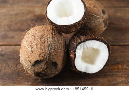 Half coconuts on rustic wooden table, close up view. Tropical exotic fruit, dessert, gourmet concept.