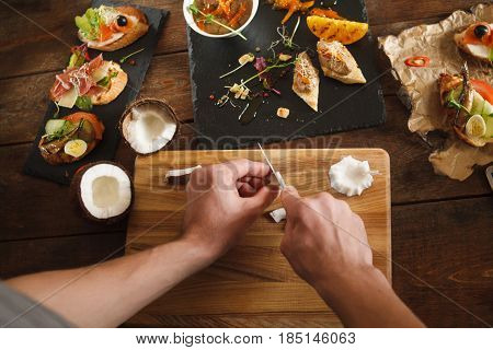Hands cutting fresh white coconut on wooden cutting board, flat lay, chef pov. Decorating dishes, culinary masterpieces, restaurant kitchen concept