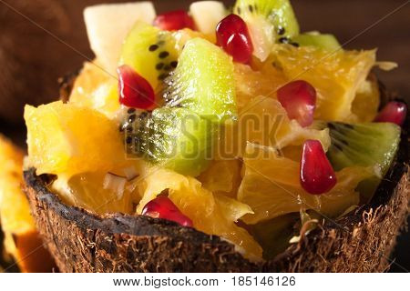 Juicy colorful fruit salad chopped in coconut shell close up view. Appetizing and tasty vegetarian dish, healthy food. Bright dessert background