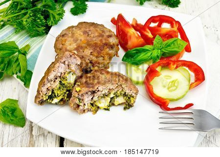Cutlets stuffed with spinach and egg, salad with tomatoes, cucumber and pepper in a plate on a napkin, basil and parsley on a wooden board background