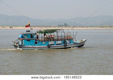 MANDALAI, MYANMA - DECEMBER 21, 2016: Boat with European tourists on a river walk along the Irrawaddy River. Burma