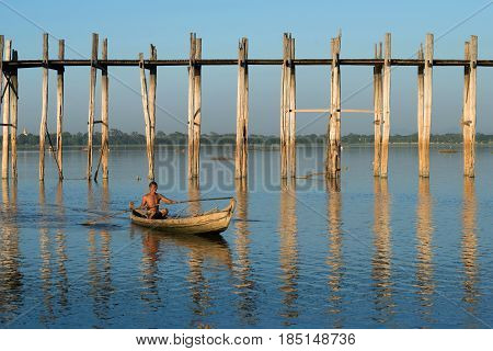 MANDALAI, MYANMA - DECEMBER 20, 2016: A burmese man swims on a traditional wooden boat at the old U Bein bridge on the Thaungthaman Lake