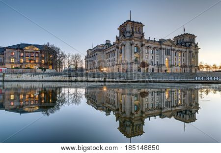 The Reichstag at the river Spree in Berlin at dusk