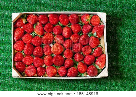A group of strawberries inside a wooden box resting on a background of (artificial) grass. Very detailed photo taken with macro lens, full of details.