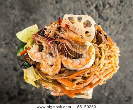 Udon noodles with shrimps over concrete background