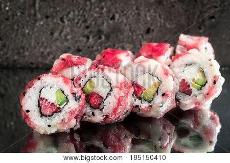 Tuna scallop roll with strawberry and avocado over gray concrete background