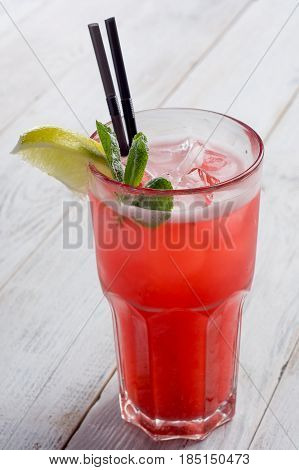 Red Cocktail with ice and lime on white wooden background.