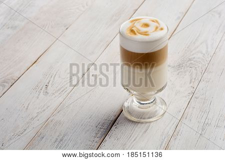 Llatte macchiato coffee on white wooden background with copy space.