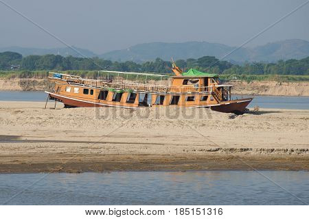 An old river ship on a sandbank on the Irrawaddy River, Myanmar
