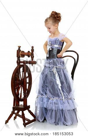 Beautiful little blonde girl dressed in a Princess dress. A girl stands near the old spinning wheel, and was staring down at her.Isolated on white background.