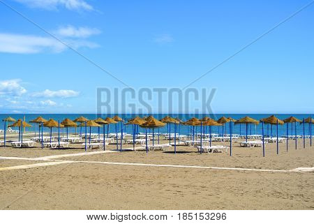 Summer Holiday View Of A Mediterranean Beach Prepared For A Tourist Season, A Sandy Beach By The Blu