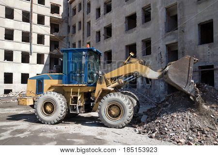 Heavy forklift front loader is working on the reconstruction of an old residential house