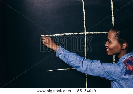 Afroamerican young smiling girl play tic tac toe game with white chalk on black board, close up. Fun, entertainment, leisure, strategy concept.