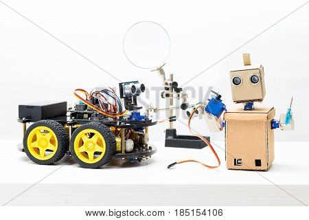 Two robots stand on the table. Robot holds servo and prop