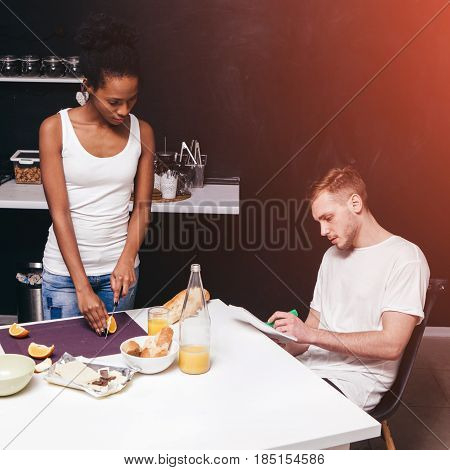 Family everyday life and values. A young interracial couple in the kitchen in a domestic setting is preparing a healthy meal together. Modern interior in the background with a free space