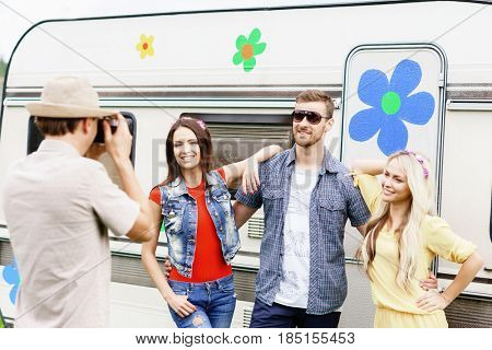 Happy friends taking pictures of each other on a road trip. Trip, holiday, vacation, spare time concept.