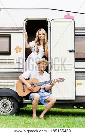 Beautiful couple having a great time outdoors. Laughing, singing, playing guitar. Trip, holiday, spare time concept.