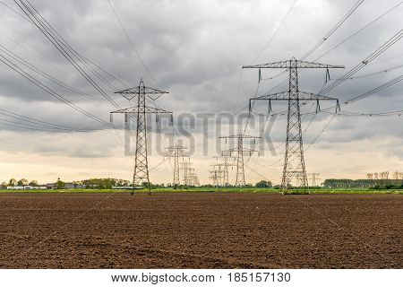 Converging high voltage cables and steel pylons in an agricultural Dutch landscape on a cloudy day in the spring season.