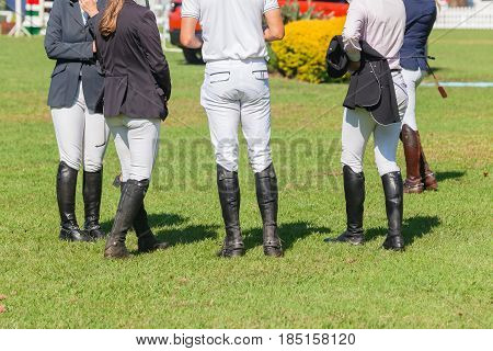 Equestrian show jumping riders closeup abstract boots spurs dress in arena
