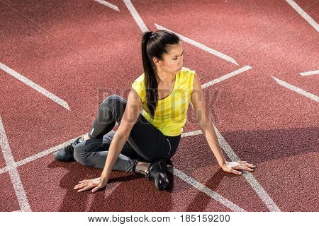 Woman sprinter doing warm up exercise before sprint