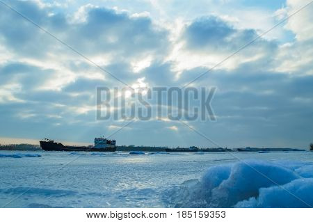Barge on frozen city river in winter