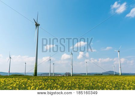Wind farm in a blooming rapeseed field seen in Germany