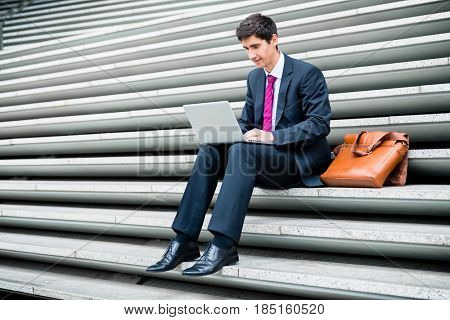Young businessman using a laptop with wireless internet connection while sitting down on stairs outdoors