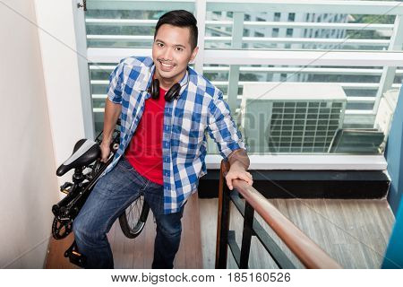 Young asian professional  coming home after work and carrying collapsible bicycle up the stairs to his apartment