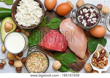High protein food - chicken, meat, spinach, nuts, eggs, beans and cheese. Products for healthy balance diet. top view