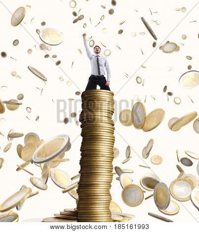 Happy businessman exults over a stack of golden coins