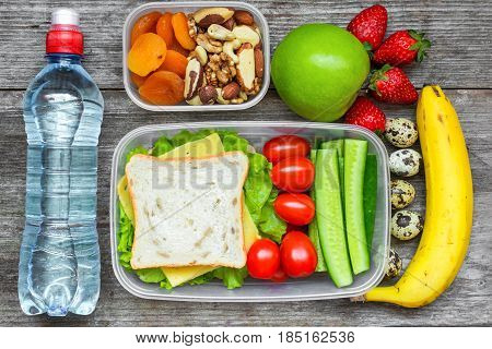 Healthy lunch boxes with sandwich, eggs and fresh vegetables, bottle of water, nuts and fruits on rustic wooden background. top view