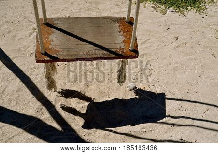 The shadow from a wooden swing is cast upon the fine sand