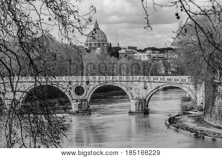 Sisto Bridge and the dome of Saint Peter. Rome Italy. Rome's historic center. Detail of a famous bridge in the Trastevere area in Rome. Basilica of Saint Peter and the Tiber River. Black and white