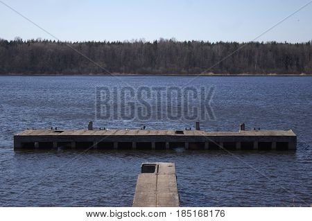 Ruined river pier on backdrop dark water with leafless forest and gray sky