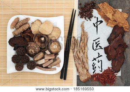 Chinese herbal medicine selection with chopsticks and calligraphy script on rice paper. Translation reads as chinese herbal medicine.