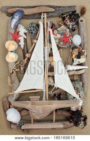 Decorative wooden sailing boat on abstract background with driftwood, seashells, rocks and seaweed on sand.