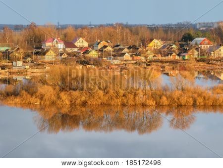 Beautiful rural spring landscape - small village in spring time at sunset, bird's eye view, soft focus processing. Spring natural rural background with countryside near the spring river in sunny spring weather. Sunset spring landscape view of rural places