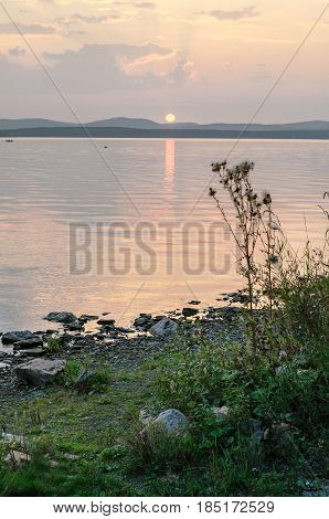 Summer sunset landscape of Irtyash Lake in Southern Urals Russia - the summer sun setting over the mountains and lake waters. Summer water sunset nature in quiet summer evening -summer view of evening lake