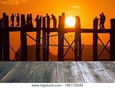 vintage wood terrace with view of silhouette of tourist crossing on the longest bridge in the world U-Bein Bridge Mandalay Myanmar.