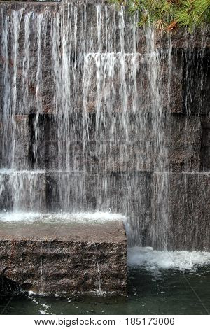 Peaceful image of stone background and several steps with  the splash from waterfall.