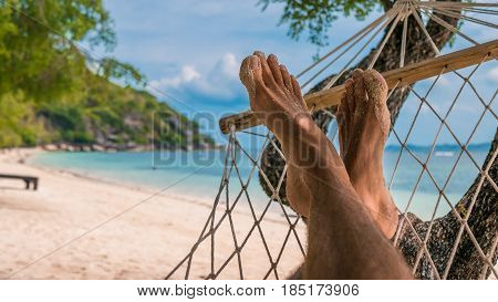 Men feet in Hammock, relaxing on the beach in Haad Rin, Ko Phangan. Thailand
