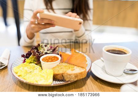 Woman taking photo with cellphone in restaurant