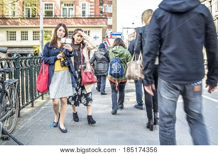 AMSTERDAM , NETHERLANDS - APRIL 31, 2017 : Tourists taking selfies while people walking around in the streets of Amsterdam