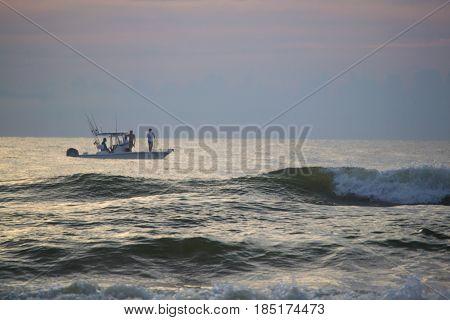 Men sport fishing just off the Florida coast at sunrise.