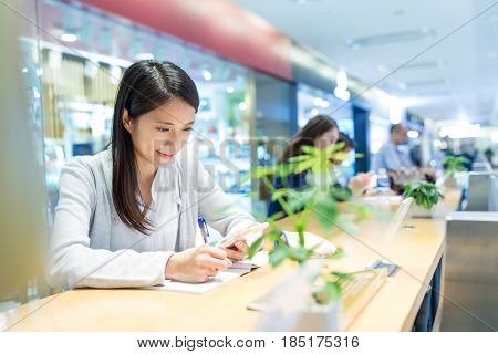 Woman taking note in coffee shop